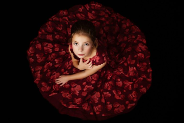Girl sitting on floor in a red dress which forms a circle around her.