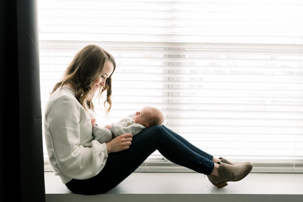 Portrait of women holding newborn in window seal.