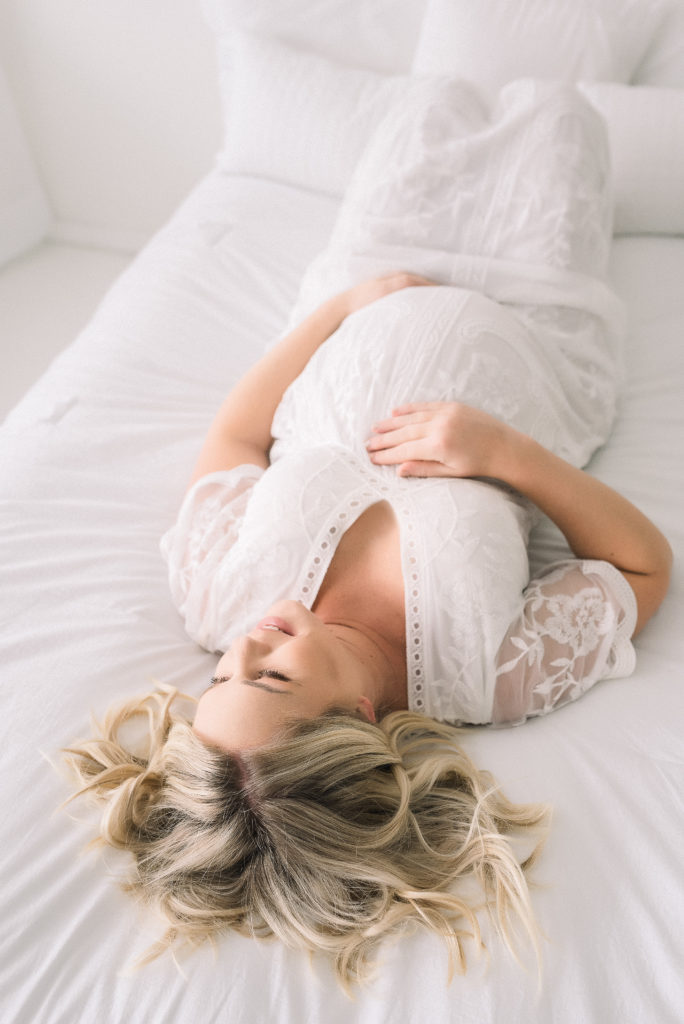 Portrait of pregnant women laying down and holding her stomach.