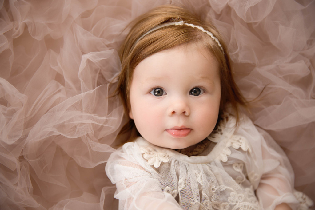 Little girl looks up in a pink dress.
