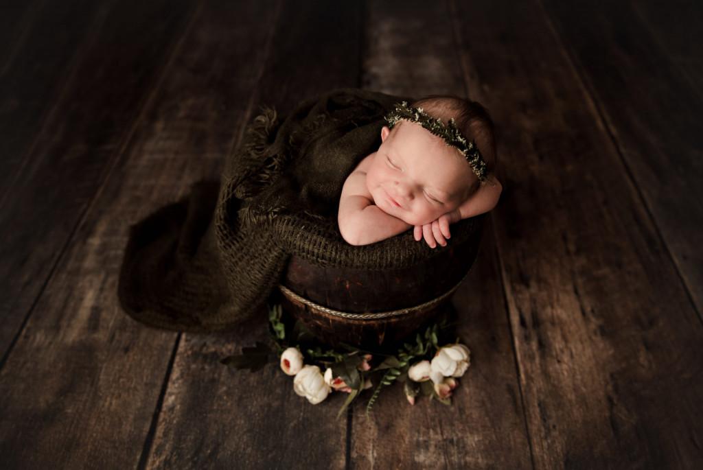 Newborn baby sleeping in a decorative bucket.