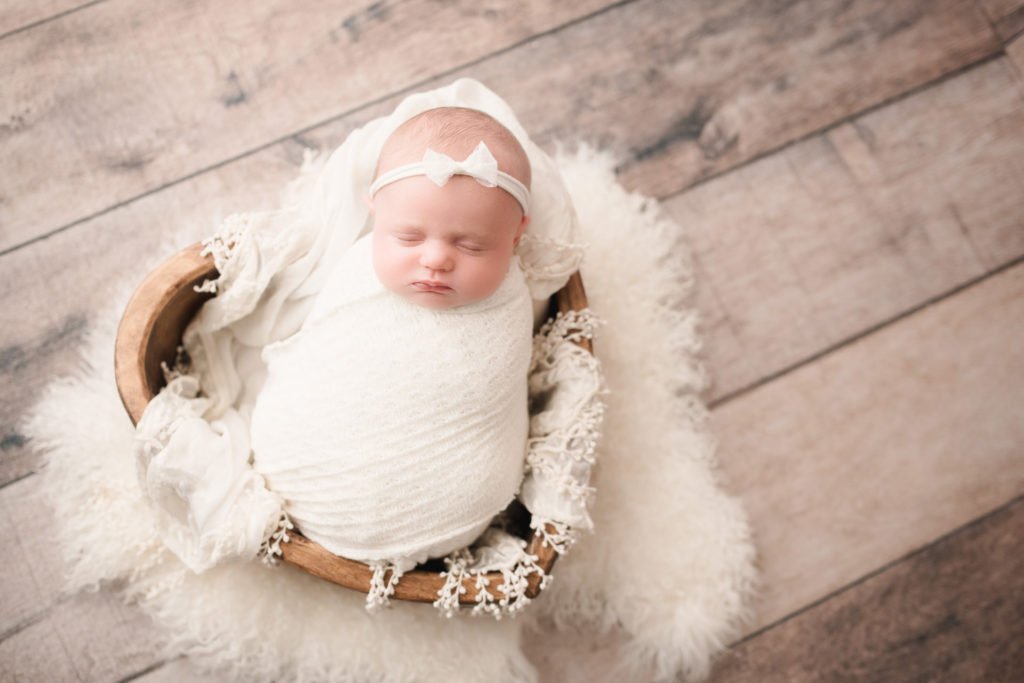sleeping baby in white swaddle in a heart shaped bucket.