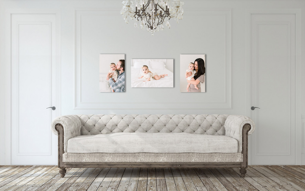 A couch in front of a wall with three pictures all involving a newborn and their parents.