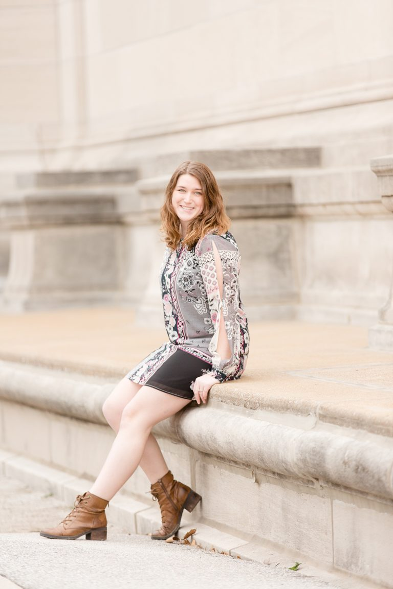 Woman sitting on courthouse steps outside.