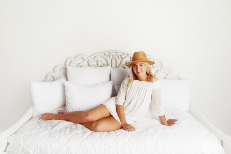 Woman in a white dress sitting on a white bed horizontally.