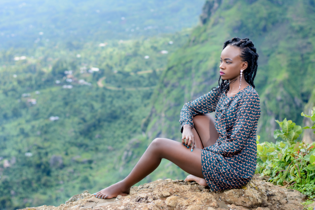 a girl sitting on a rock overlooking wooded mountains